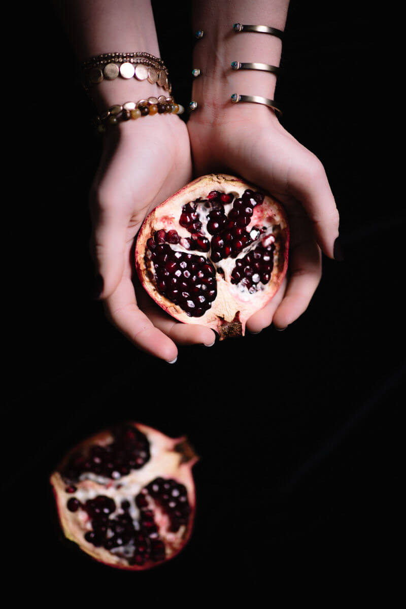 close up of red pomegranate and gold jewelry  on dark black background