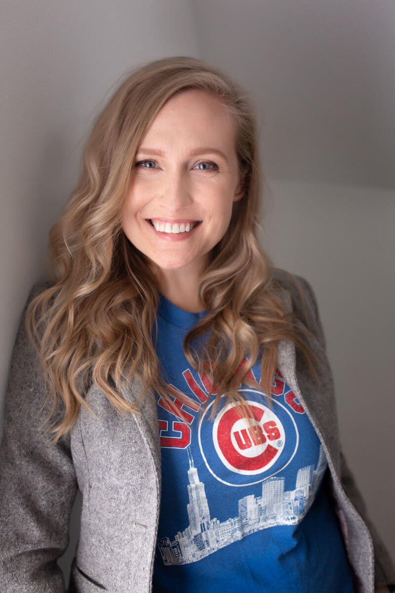 professional personal branding photo of blonde leaning on wall wearing a cubs shirt and tweed blazer