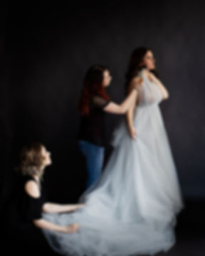 assistant and make up artist helping bride in long tulle dress