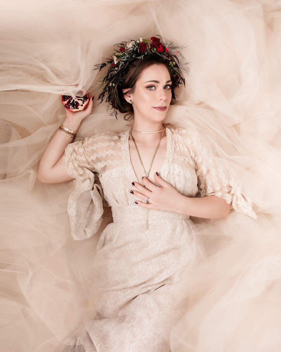 bright and airy persephone photo laying in bed of tulle with pomegrante