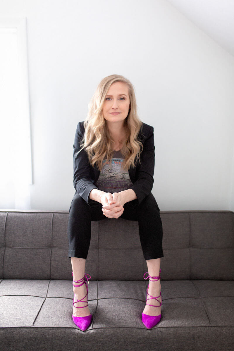 strong powerful professional business photo with blonde sitting on sofa with pink heels