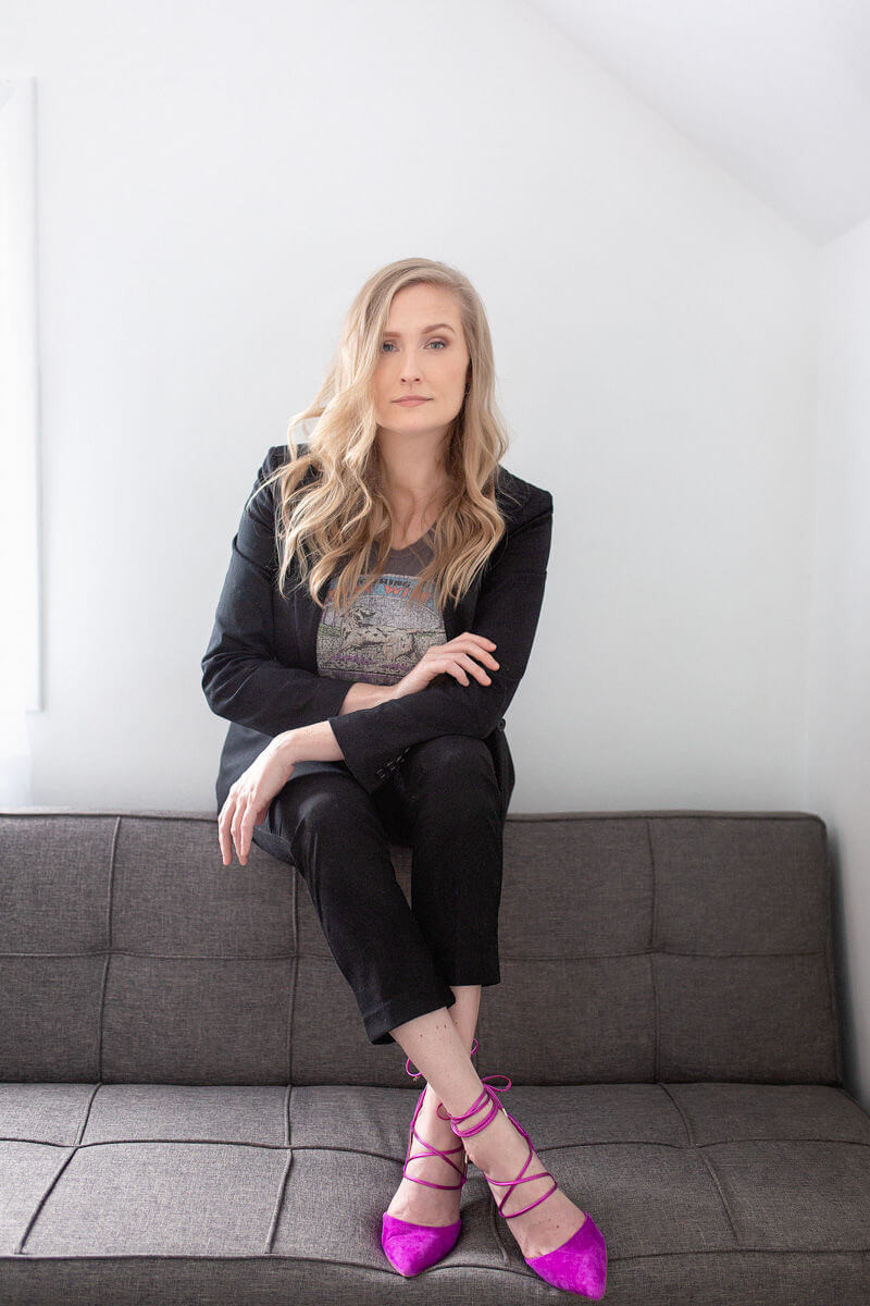 strong professional business photo with blonde sitting on sofa with pink heels
