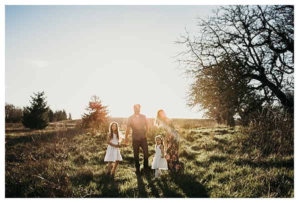 backlit sunset family photos with warm golden hour sunrays on grassy hill