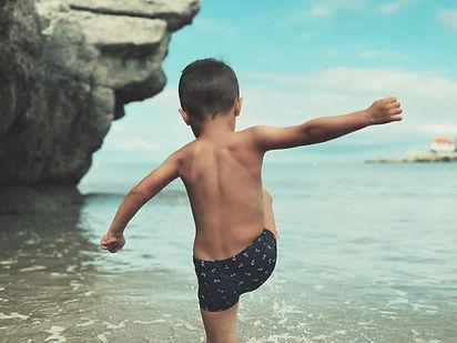 Photographie d'un petit garçon jouant sur une plage