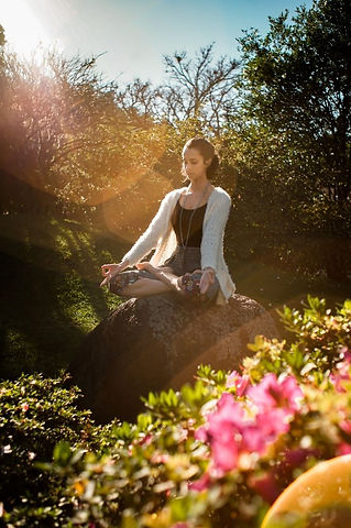 Woman Meditating on Rock and practicing