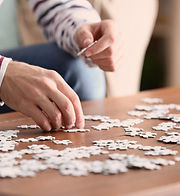 Young man doing jigsaw puzzle at home, c