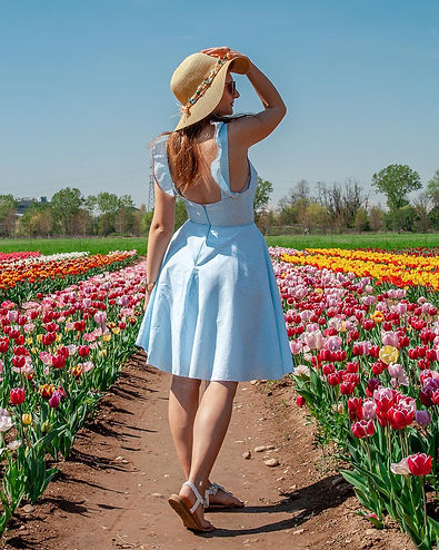 Ditsy print blue dress in a field of tulips