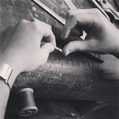 Close up image of hands at the workbench, rehairing a violin bow