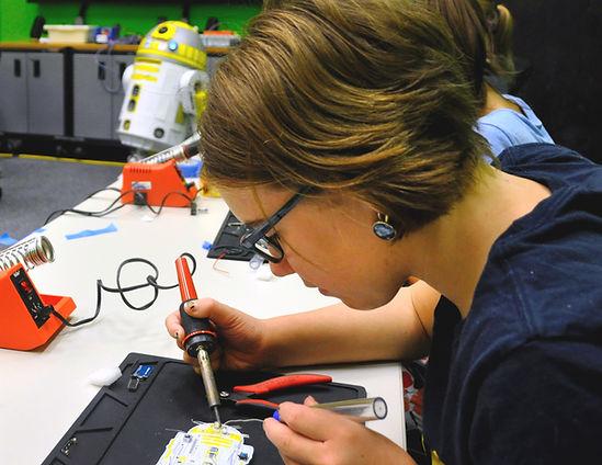 Student solders circuit board