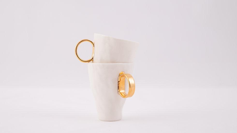 dwa espresso z białej porcelany o złotym uszku