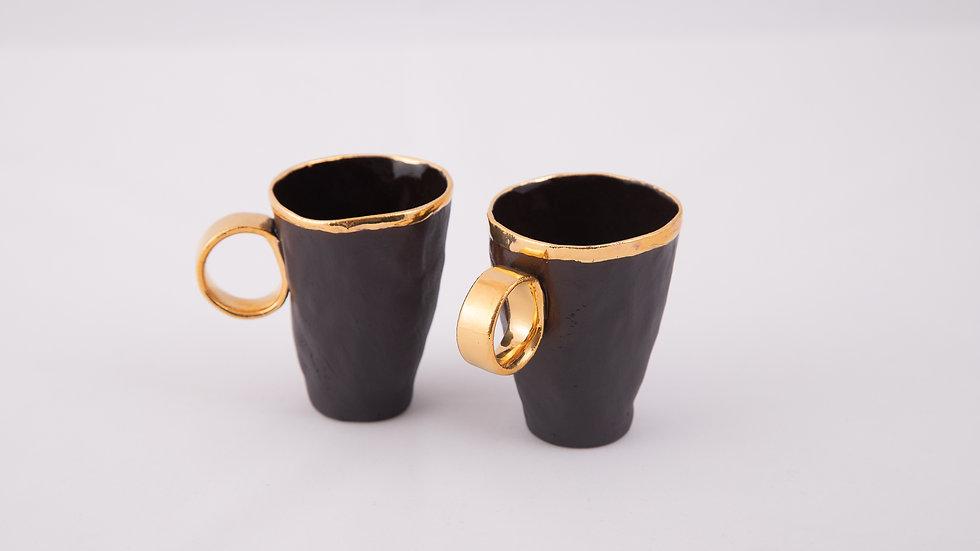 dwa espresso z czarnej porcelany o złotym rancie i złotym uszku