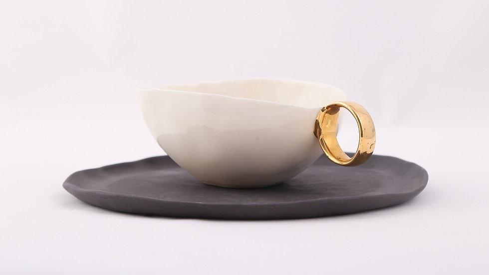filiżanka z białej porcelany w zestawie z czarnym matowym talerzem