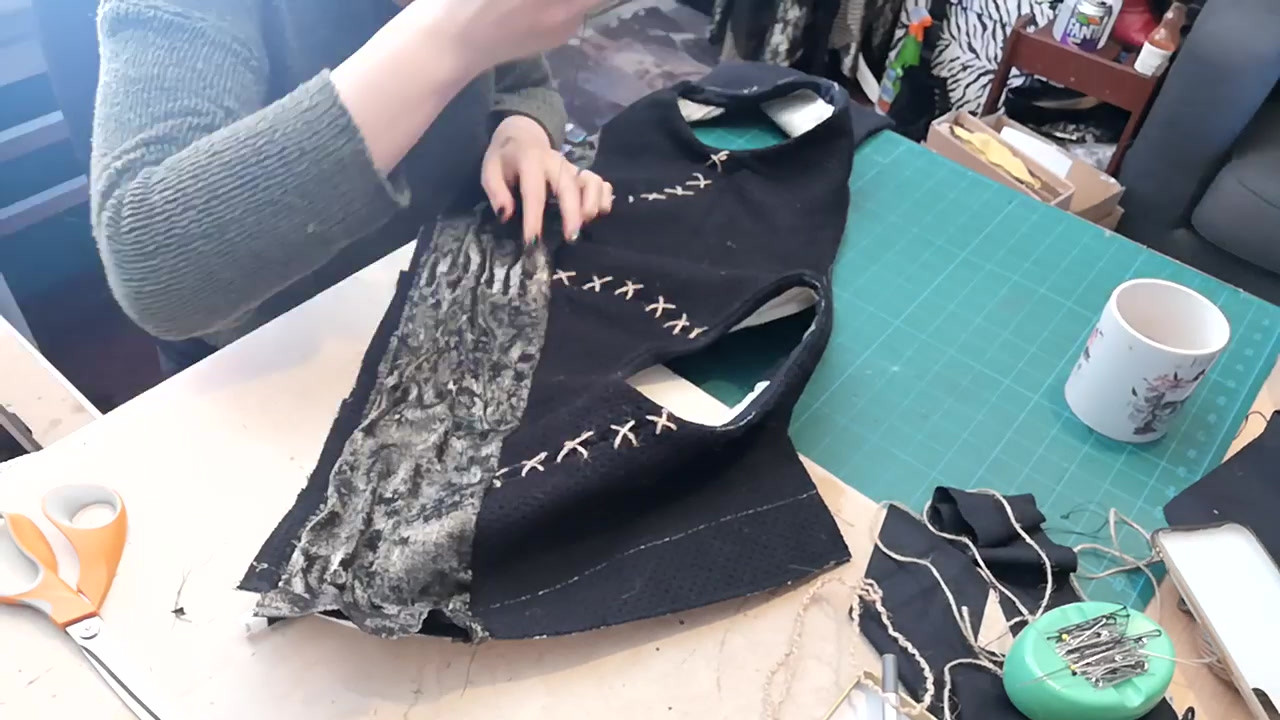 Hand stitching the gold ruched belt onto