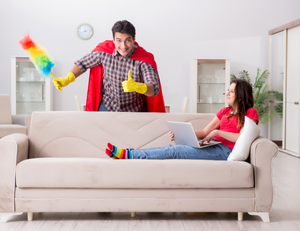 Husband in a cape and holding cleaning supplies as his wife relaxes on the couch
