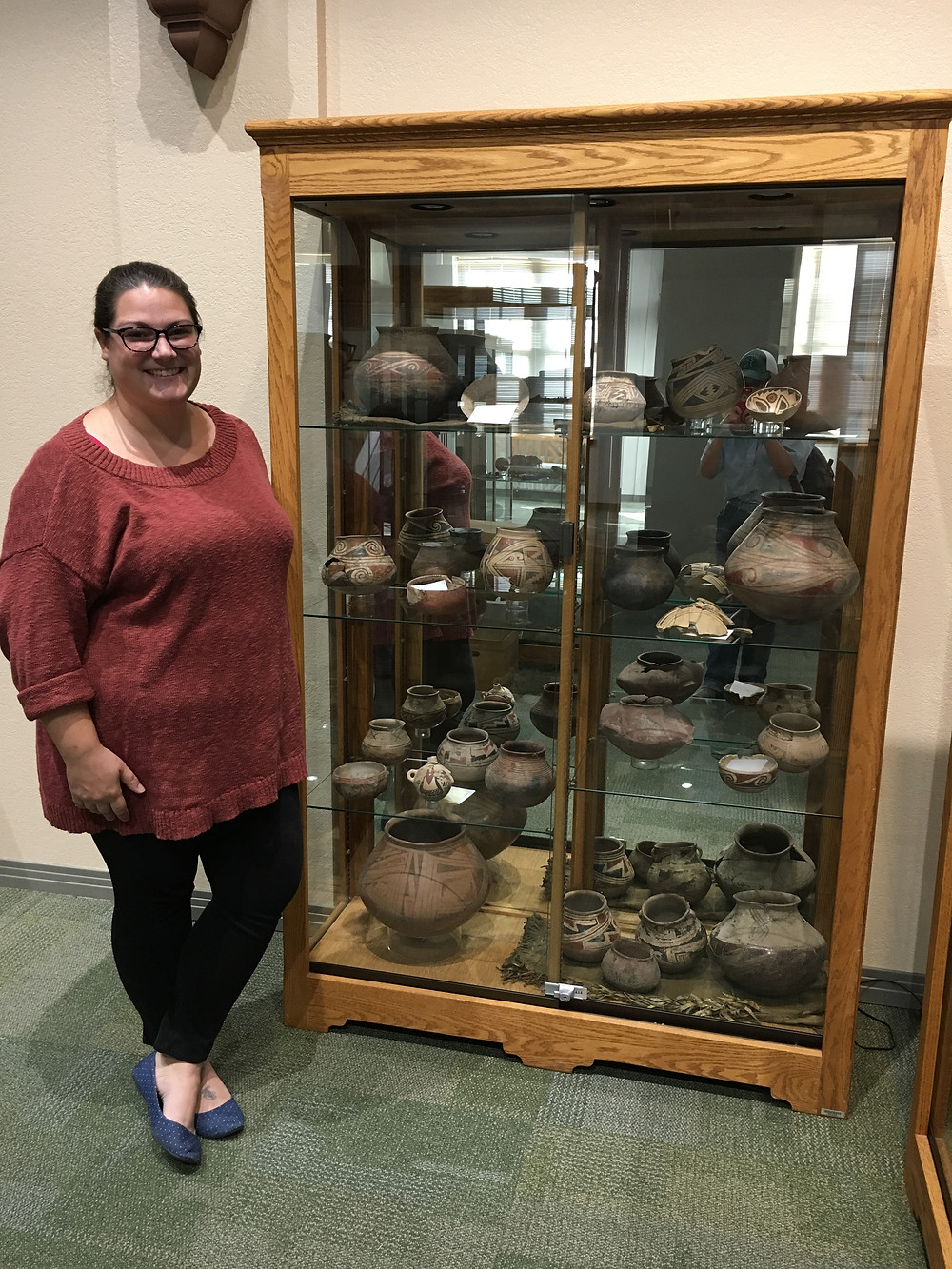 Jenna Domeischel, the Curator of the Blackwater Draw Museum, standing in front of her favorite case of pottery displayed in the museum. Photo by Jena Slater