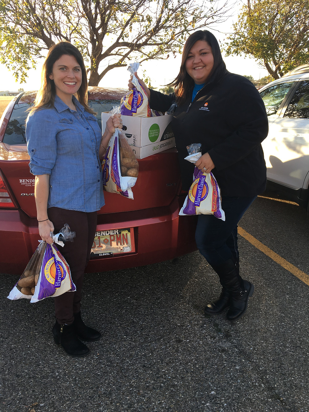 Kaitlyn White, Marketing Director at La Casa Services and Coordinator for Thanksgiving Basket Distribution and Celina Stroup, HR at La Casa unloading the 10 bags of potatoes Stroup brought in for the Thanksgiving Baskets. Photo by Jena Slater