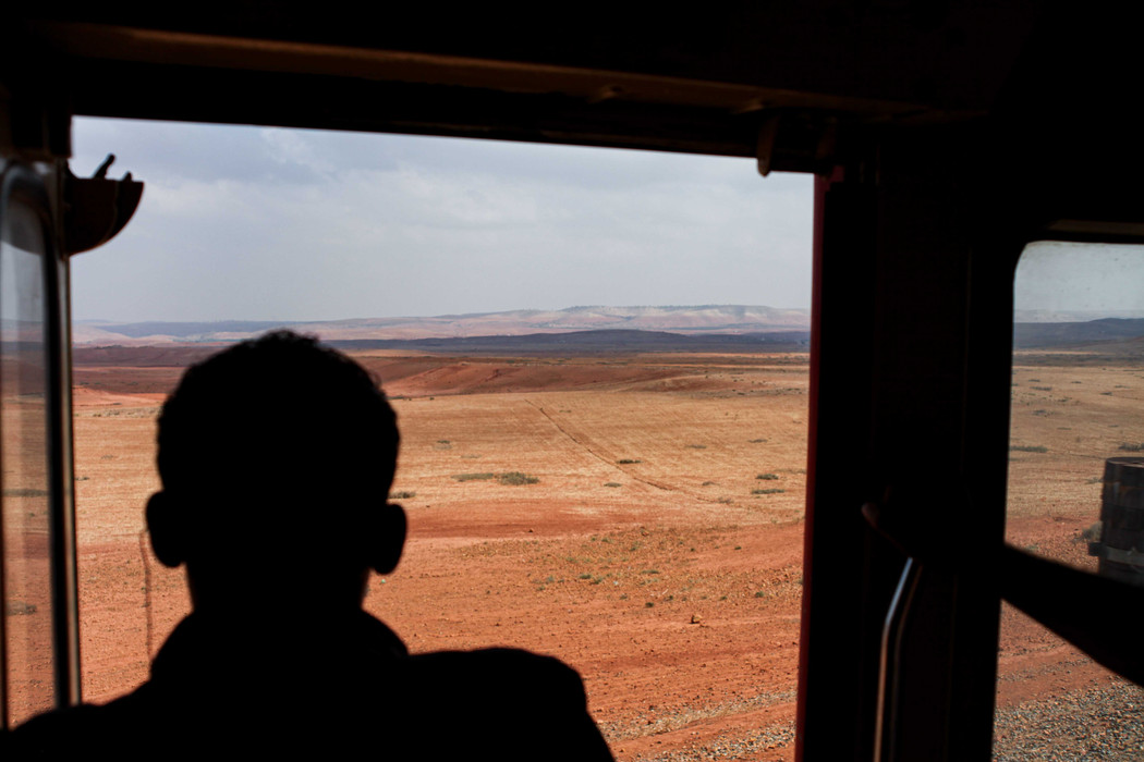 A young man looks out of the open train door into the desert.