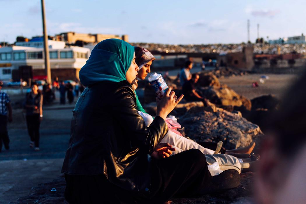 Young women enjoying the sunset on the beach of Rabat.