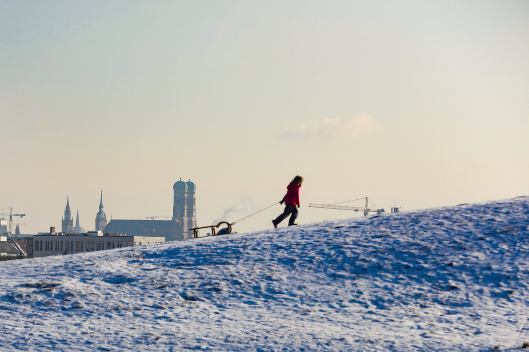 A child pulls a sled up the Olympic hill in Munich. In the background the Frauenkirche.