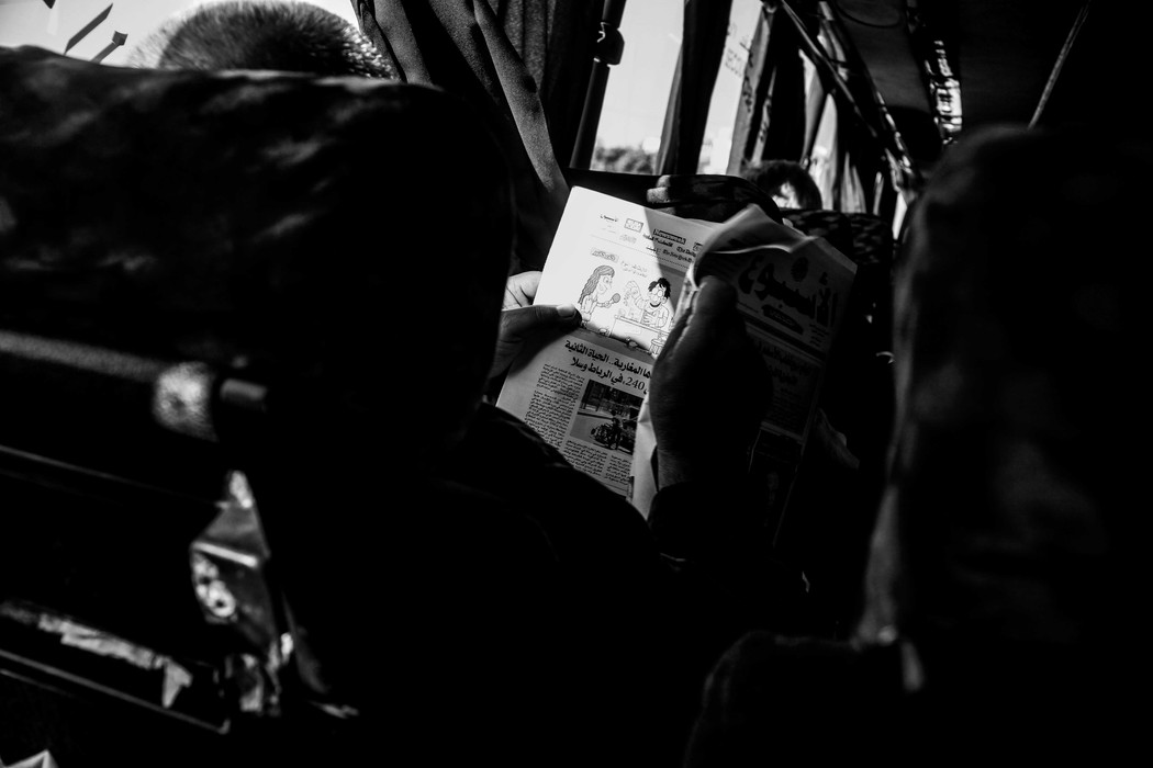 A man is reading a newspaper on a bus.