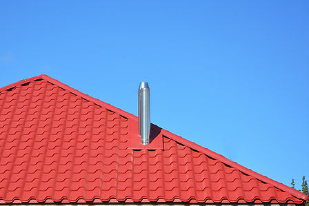 Chimney coming out of a red roof