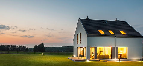 a brighly lit home at dusk