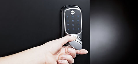 a hand turning a door lock that has a keypad