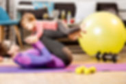 A woman laying on a yoga mat with a baby resting on her legs