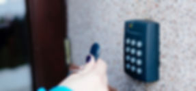 a hand holding a keyfob passing in front of an alarm system