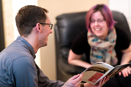 A man and woman laughing and looking at a brochure