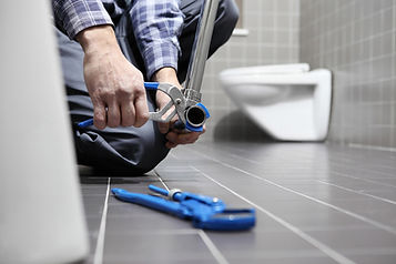 A plumber cutting a pipe with pipe cutters