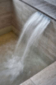 water pouring out of tile opening into a bath