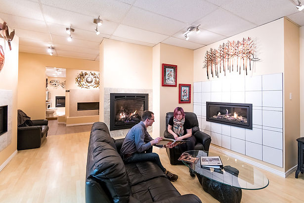 two people sitting on a sofa and chair in Fraser Plumbing and heating looking at brochure about a DaVinci custom fireplace