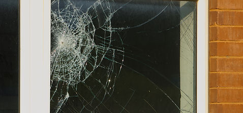 a pane of glass that is shattered in a window sill