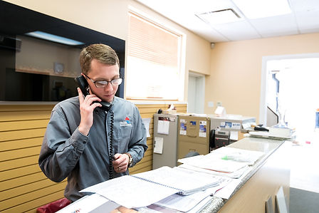 A man on the phone standing at the counter of Fraser Plumbing and Heating
