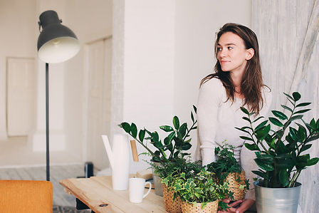 A woman smiling looking off camera standing behind some plants resting on a table