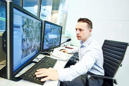 a man sitting in front of two large computer monitors typing on a keyboard