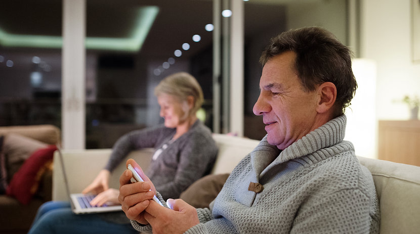 two elderly people on a smart phone and laptop