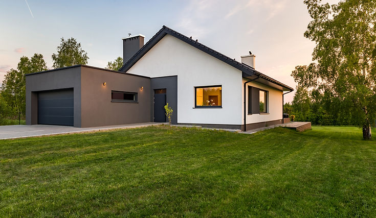 a modern home and garage with manicured lawn