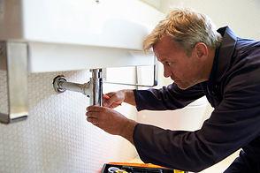 A plumber tightening a bolt underneath a sink