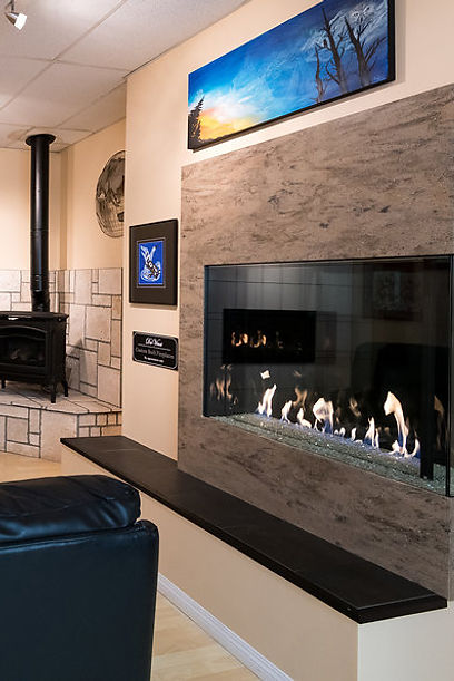 A freestanding stove and a DaVinci fireplace featured in the Fraser Plumbing showroom.