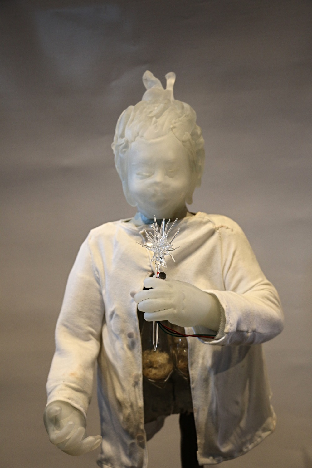 A hand blown glass sculpture of a girl wishing on a dandelion