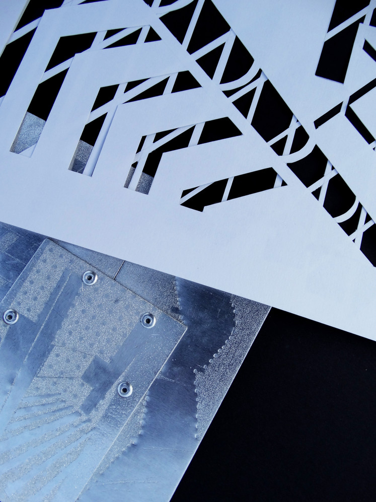 layered paper cut-outs against layered and riveted metal pieces