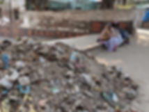 widows sitting in Radha Kunda next to a pile of trash
