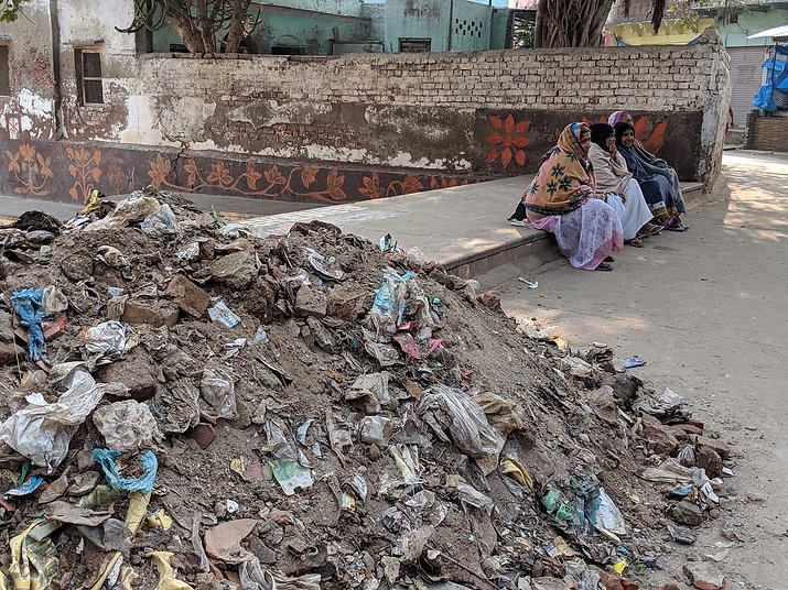 widows sitting in Radha Kunda next to a pile of trash