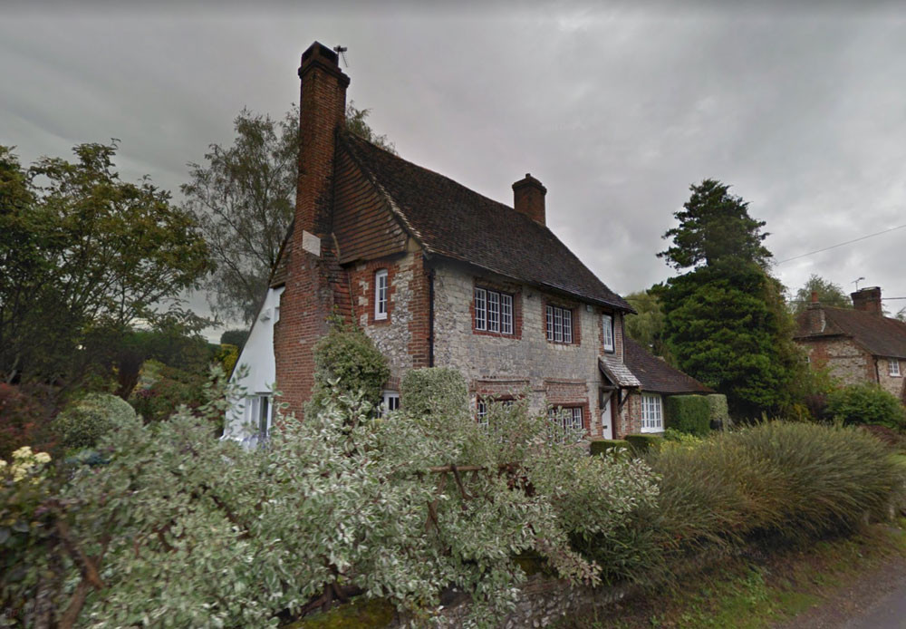 a stone and brick house in Graffham, West Sussex, on a cloudy day