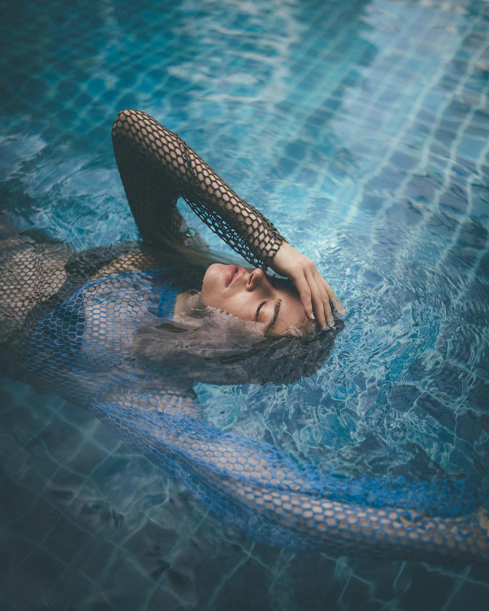 woman feeling her forehead inside a pool