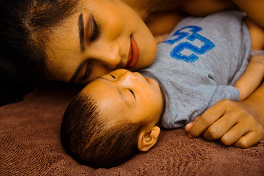 woman and her toddler lading on a blanket