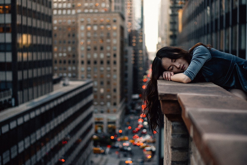 woman resting her head on the ledge of a wall on a building