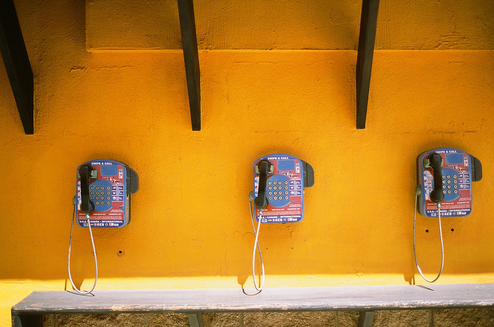 Payphones on a yellow wall